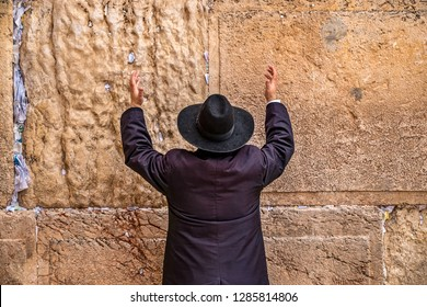 Believing Jew pray near the wall of crying in a big black hat raising his hands uphill