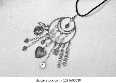 Believing in magic protecting the holder of amulet. Jewelry charm or talisman. Name amulet for good luck. Luck amulet on textile background. Silver amulet with gems and pendants. Repelling bad luck.