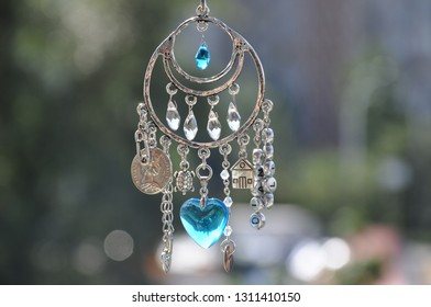 Believing in magic protecting the holder of amulet. Name amulet for good luck. Luck amulet hung out outdoor. Silver amulet with gems and pendants. Jewelry charm or talisman. Forget bad luck.