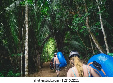 Belize, Belize/Central America - May 5th 2017: Young woman and man wearing helmets and holding tubes in the jungle on an excursion