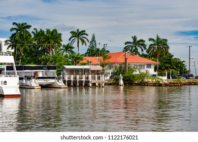 Belize City, Belize - December 2015: Boats, palm trees, and buildings line the seaport.