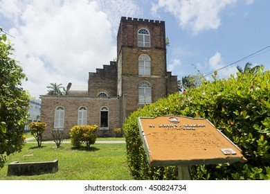 Belize City, Belize - June  24, 2016: Standing by the information panel in front of St John's Anglican Cathedral in Belize City.