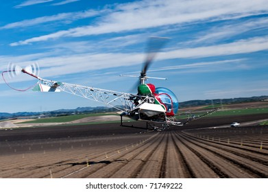 Bell 47 helicopter spraying crops in the Salinas Valley, California