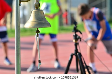 The bell for the athletics competition with the athletes in the background