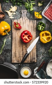 Bell colorful paprika peppers cooking preparation. Paprika on wooden cutting board with kitchen knife, minced meat, egg and seasoning on dark rustic background, top view