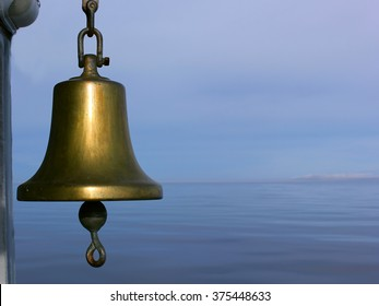 The bell at front with the still water and the blue cloudy sky with the clear horizon on the background at the silent late evening.