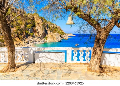 Bell hanging on tree and view of Kyra Pynagia beach from church terrace on Karpathos island, Greece