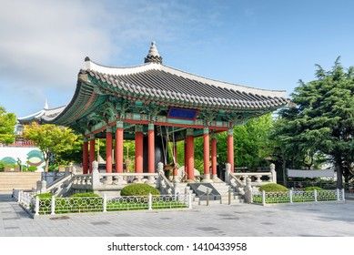 Bell pavilion of traditional Korean architecture on blue sky background at Yongdusan Park in Busan, South Korea.