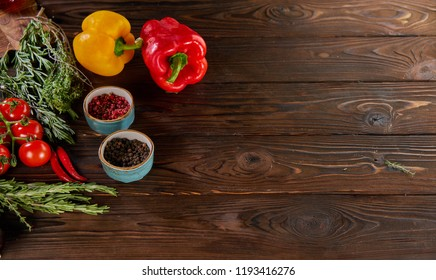 bell peppers, rosemary, cherry tomatoes and other ingredients for cooking on wooden rustic background top view