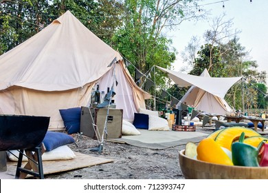 Bell Tent decoration in camping party with stove and vegetable in foreground and many accessory for camping night.