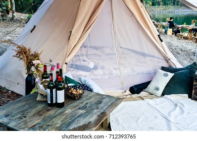 Bell Tent decoration in camping party with many wine bottle in front of tent ,someone waiting for the camping started in background.