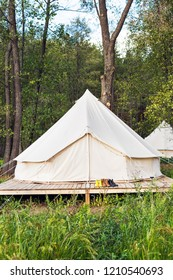 Сanvas bell tent with shoes on a wooden base at the forest