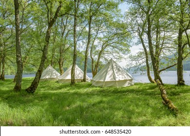 Bell tents at erected at a woodland beside Loch Voil in Scotland.