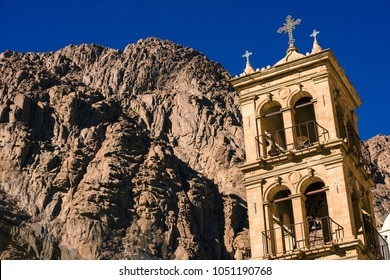bell tower of the ancient Orthodox monastery with a cross on the top of the rocky mountains