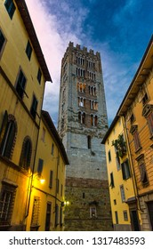 Bell tower of Chiesa di San Frediano catholic church view through narrow street with lamp light in historical centre of old medieval town Lucca, evening view, Tuscany, Italy
