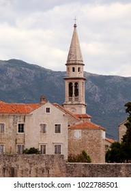 The bell tower of the Church of Saint John and a fragment of the wall of the Old Town of Budva at dawn, Budva, Montenegro