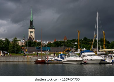 The bell tower of the Church of St. Olav and the center of Tallinn, Estonia, seen from the port with a stormy sky in the background
