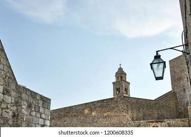Bell tower of a church and walls around it on the blue sky background in old town of Dubrovnik in Croatia. There is a hanging vintage lantern on the right wall. Outdoors. Horizontal.