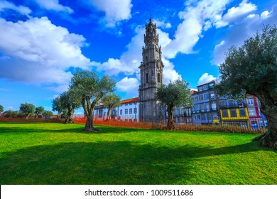 Bell tower of the Clerigos Church (Church of the Clergymen), a baroque church in backlit winter sunbeam. Old olive trees and green grass lawn on foreground. City of Porto, in Portugal.