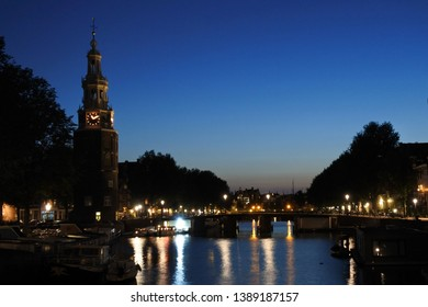 bell tower at dusk in amsterdam with city lights