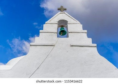 Bell tower at a Greek island against blue sky background.Green bell with Christian cross at a whitewashed bell tower of an Orthodox church at Mykonos island.