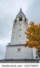 Bell tower of the Holy cross Church in 1774 on the background of red-yellow leaves and cloudy sky.
