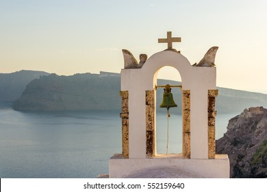 Bell tower of orthodox greek church in Oia on Thira (Santorini) island with sea on the background