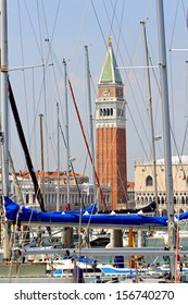 bell tower of St. Mark in the midst of so many masters of trees yatch and ships moored in the port