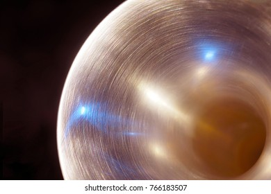 Bell of trumpet with white and blue highlights on a dark background; toned in cooper