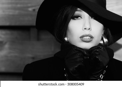 Bella donna concept. Close up portrait of beautiful model wearing black hat and coat. Hands in leather gloves holding collar. Silver accessories. Monochrome outdoor shot