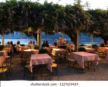 Bellagio, Lake Como / Italy - June 10 2018: People dining at harbor side restaurants in Bellagio, Lake Como