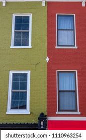 Belleville, IL—June 10, 2018; Four windows forming pattern on two connecting red and green painted brick buildings. Belleville is known for 1800s brick architecture