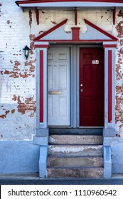 Belleville, IL—June 10, 2018; red and white doors entering brick building with chipped white paint.  Belleville is know for its historic registry buildings from the 1800s.