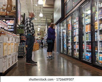 Bellevue, WA / USA - circa April 2020: People wearing face masks while shopping for beer and liquor inside a Total Wine and More beverage shop in downtown Bellevue.