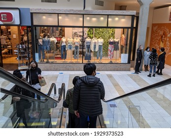 Bellevue, WA USA - circa March 2021: People wearing face masks descending on an escalator at the Bellevue Mall.