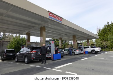 Bellevue, WA, USA - March 10, 2021: People in cars waiting in long lines to fill up vehicles with gas at Costco Gas Station.