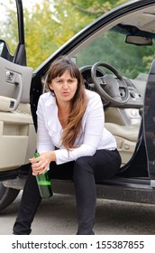 Belligerent drunk woman sitting in the open door of her car on the sill glaring at the camera as she clutches her bottle of alcohol