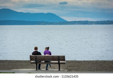 BELLINGHAM, WA/U.S.A. - AUGUST 1, 2106: An unidentified couple sit on a bench  on a beach area in Boulevard Park, with a view of Bellingham Bay.