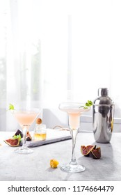 Bellini cocktail with peach and figs, honey on light background over windows, copy space