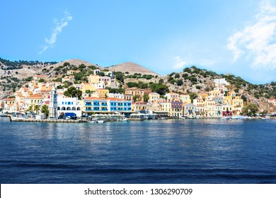 Bell-tower and colorful neoclassical houses in harbor town of Symi (Symi Island, Greece)