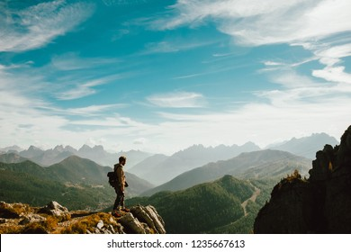 Belluno, Italy - 20 october 2018: - a young man standing over top of mountain canyon watches dramatic big valley extend in front of him making a step forward
