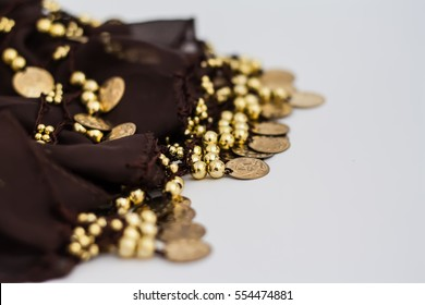 Belly dance belt isolated on white background, brown scarf with golden coins. Blurred photo, selective focus.