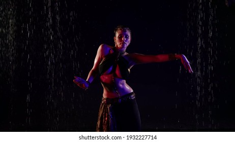 belly dance under rain, woman is dancing slowly in darkness, traditional oriental dance performance