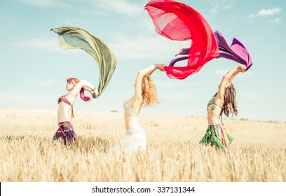 Belly dancer group in action . Belly dancer girls performing in a wheat field. concept about fashion and discipline