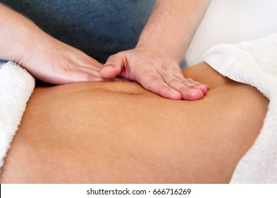 Belly massage in massage studio. Close up of hands massaging female abdomen. Masseur massaging girls belly. Therapist applying pressure on belly. In spa center. Body and health care, medicine concept.
