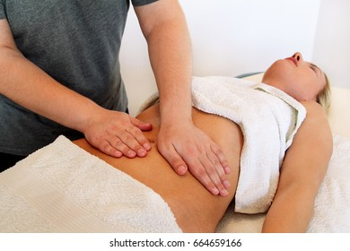 Belly massage in massage studio. In spa professional wellness center. Masseur massaging girls belly. Body and health care, medicine concept. Pretty women having massage in the spa body massage salon.