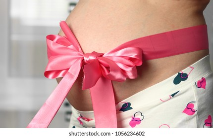 Belly of pregnant woman with pink bowknot.