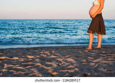 Belly of pregnant woman walking on the beach, sea in the background.