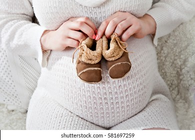 belly of a pregnant woman in white sweater, mother hands holding shoes for the newborn girl