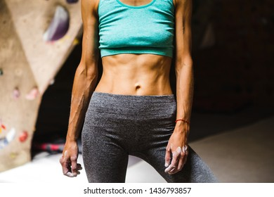 The belly of a slim woman close up. Female press. A drop of sweat on a thin sports stomach. Training on the climbing wall. Strong female hands. Woman trained in the gym.